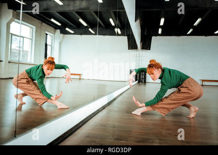 Pretty red-haired professional dancer dancing near the mirror - Stock Photo