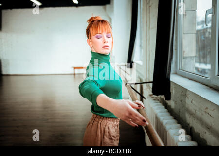 Red-haired professional ballet dancer with hair bun looking focused - Stock Photo