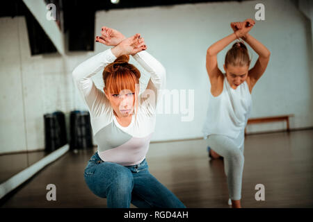 Red-haired ballet teacher and her student looking expressive - Stock Photo
