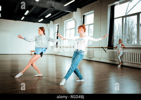 Beautiful red-haired professional dancer in blue jeans and her student dancing in the studio - Stock Photo
