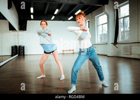 Beautiful red-haired professional dancer in blue jeans and her student moving energetically - Stock Photo