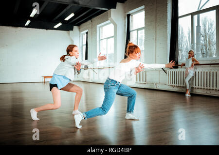 Beautiful red-haired professional dancer in blue jeans and her student dancing expressively - Stock Photo