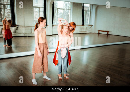 Red-haired slim dance teacher showing arm position to her student - Stock Photo