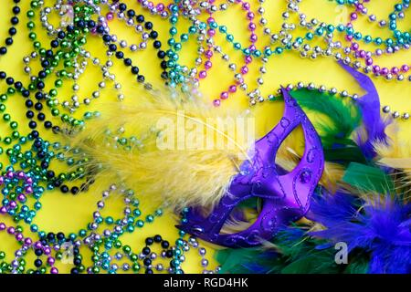 An assortment of colorful decorations for the Mardi Gras festival on a yellow background, including Venetian mask, feathered boa and Mardi Gras beads. - Stock Photo