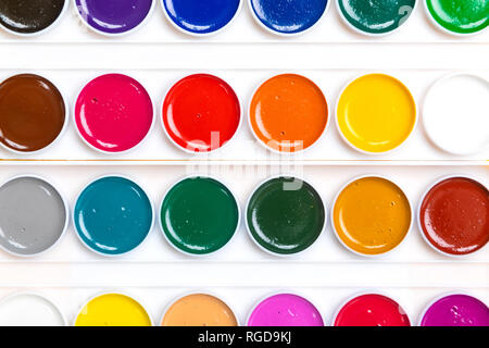 top view white palette with paints lie isolated on bright background. Place for writing. Can be used as a creative background. Bright rainbow colors - Stock Photo