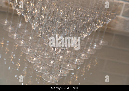Glasses in the blue light are built beautifully before the solemn event in an expensive restaurant. many empty champagne glasses close up. glass goble - Stock Photo