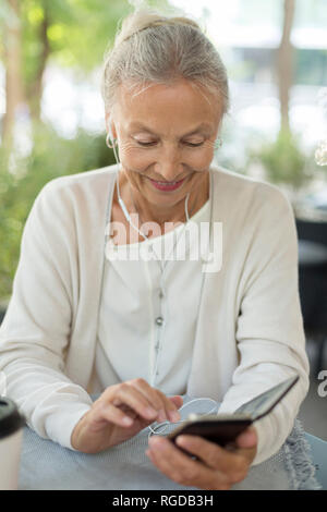 Smiling senior woman at an outdoor cafe with cell phone and earphones - Stock Photo