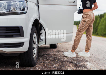 Finland, Lapland, young woman at country road getting into a car - Stock Photo