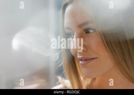 Portrait of daydreaming young woman - Stock Photo