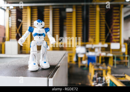 Toy robot standing on shelf in logistics center - Stock Photo