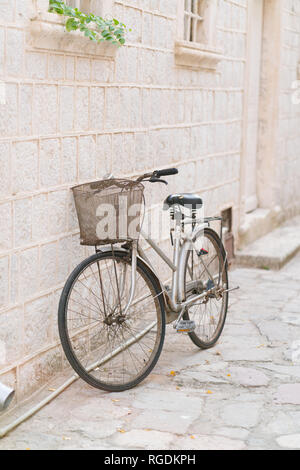 old rusty vintage bicycle leaning against a stone wall, outdoors - Stock Photo