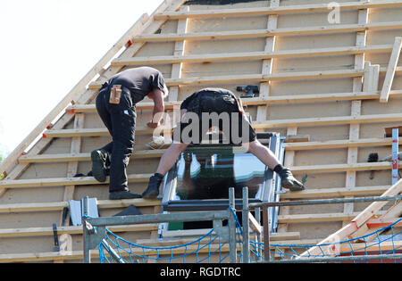 roofer installing new skylight during roof renovation - Stock Photo