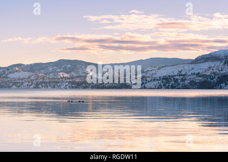 Snow-covered mountains and sunset colors reflected in still waters of lake in winter - Stock Photo