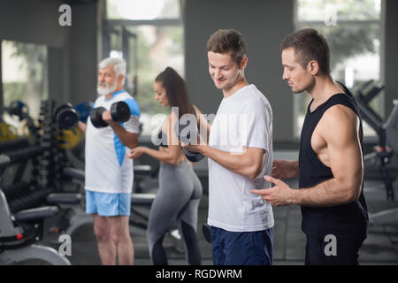 Muscular, athletic trainer helping man to do exercises with lifting dumbblells. Fit people wearing in sportswear. Female coach concentrated on elderly client working out. - Stock Photo
