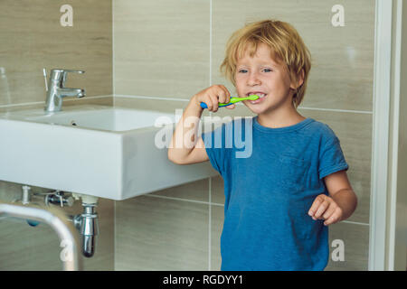 Little blond boy learning brushing his teeth in domestic bath. Kid learning how to stay healthy. Health care concept - Stock Photo