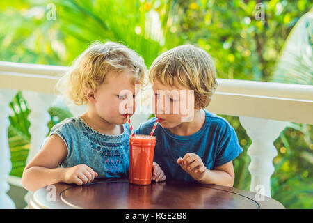 Children boy and girl drink orange smoothie from papaya - Stock Photo