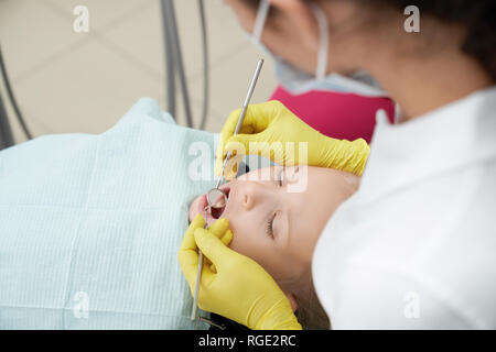 Selective focus of cute girl lying on dental chair with open mouth while female doctor examining teeth. Little child visiting doctor in clinic. Concept of dentistry and stomatology. - Stock Photo