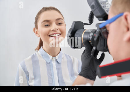 Photographer in black glowes and sunglasses taking photo of young pretty woman. Adorable and charming model showing white teeth and beautiful smile after treating in stomatology. - Stock Photo
