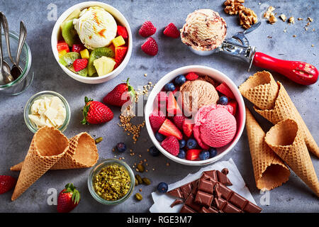 Fresh fruit with scoops of creamy speciality ice cream in assorted flavors with raspberry, berry, blueberry, strawberry, walnut , pistachio, chocolate Stock Photo