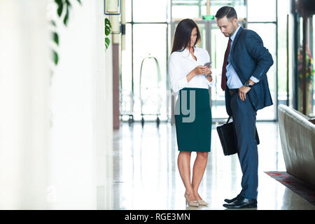 Confident business partners walking in office building and discussing work. - Stock Photo