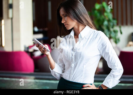 Photo business woman wearing suit, using smartphone in office - Stock Photo
