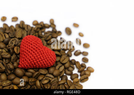 Love to coffee, Valentine heart and roasted coffee beans isolated on white background. Red knitted symbol of love, concept of romantic breakfast