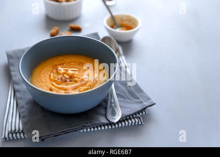 Bowl of red lentil soup on gray wooden background. Vegetarian food concept - Stock Photo