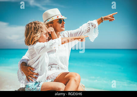 Beautiful little boy enjoying with his mother on the beach rock. They are pointing something. - Stock Photo