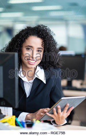 Portrait of a smartly dressed African American business woman smiling and sitting at her desk in an office - Stock Photo