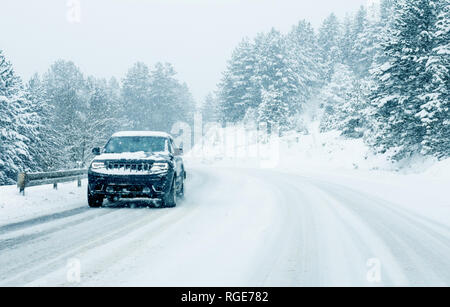 Traffic cars on winter road in snow blizzard - Stock Photo