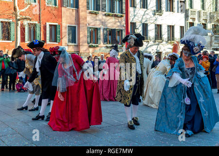 Group of people wearing typical costumes and masks dancing on small square during famous traditional annual carnival in Venice. - Stock Photo