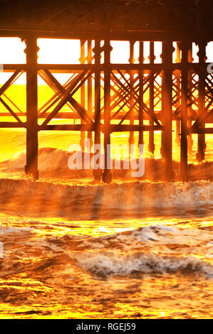 Golden shafts of light pass through the iron work underneath South Pier and into the waves of the incoming tide - Stock Photo