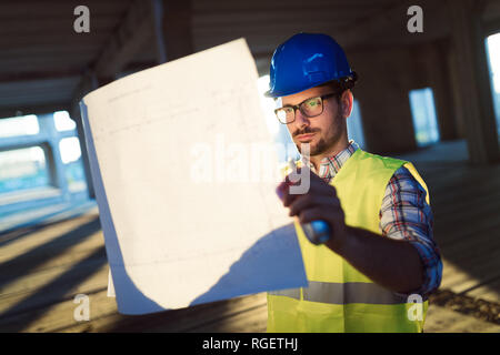 Male young architect with blueprints using walkie-talkie - Stock Photo