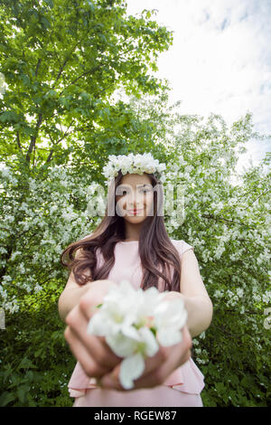 Young woman in flowers wreath  in spring blossom park outdoors. Beautiful girl outdoor portrait on foliage background - Stock Photo