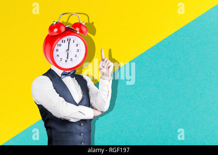 a man with a clock instead of a head on a yellow-blue background, the concept of waking up in the morning - Stock Photo