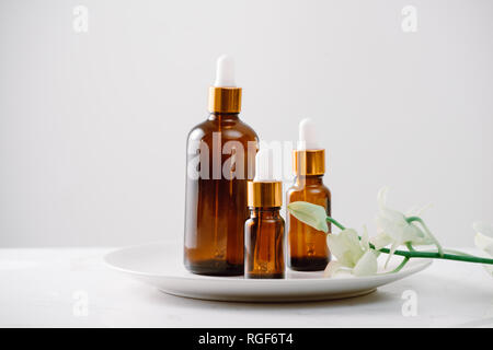 Dropper bottle of organic orchid pure oil on a white surface with orchid heads in the background. - Stock Photo