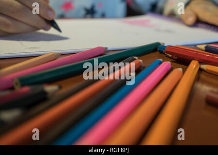 Colored pencils scattered on a wooden table. The child draws a picture in the album - Stock Photo