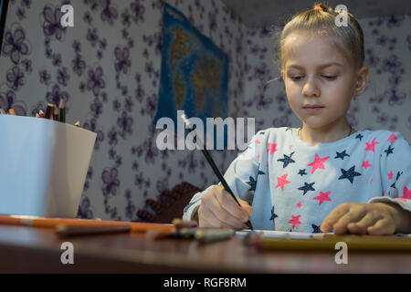 The child draws a picture with colored pencils - Stock Photo