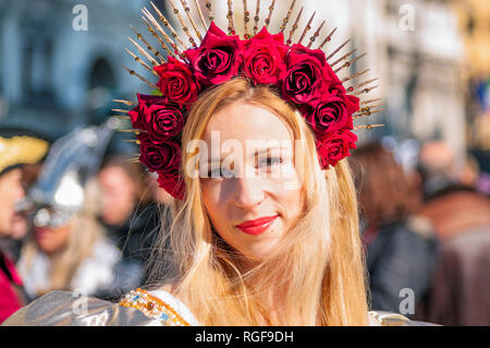 Venice, Italy - February 10 2018: Portrait of a beautiful young blonde caucasian woman wearing a crown of red roses during the Venetian carnival party - Stock Photo