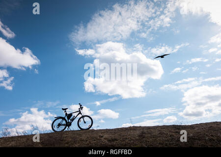 Bike silhouette in blue sky with clouds. symbol of independence and freedom with flying bird - Stock Photo