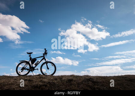 Bike silhouette in blue sky with clouds. symbol of independence and freedom - Stock Photo