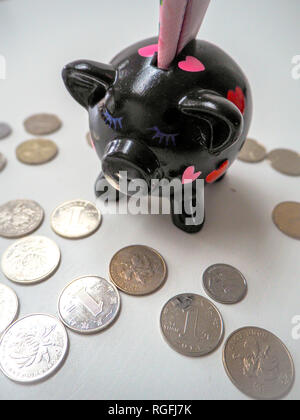 Black piggy bank filled with Chinese 100 rmb banknotes and Chinese and Hongkong coins on a white wooden background. 2019 is the year of the pig.