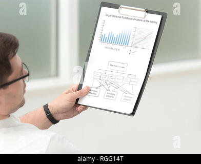 close up.serious businessman with business documents sitting near his office Desk - Stock Photo