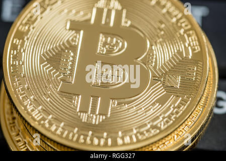 Top closeup view of  golden Bitcoin coins over black computer keyboard. - Stock Photo