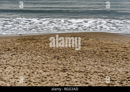 Gentle constructive waves rolling onto a sandy beach. - Stock Photo