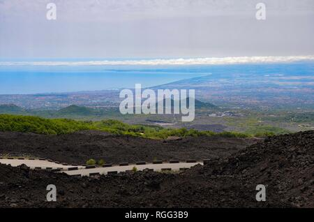 Panorama view of Catania in Sicily, mediterranean sea, view from the road up to Etna volcano, lava on both sides, blue sky, summer, sunny, coast - Stock Photo