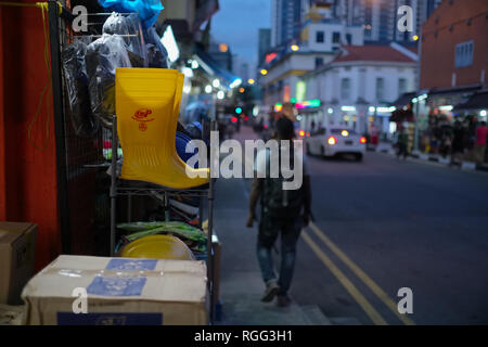 A pair of yellow rubber boots on sale in Little India area, Singapore, an area frequented by laborers and construction workers from India & Bangladesh - Stock Photo