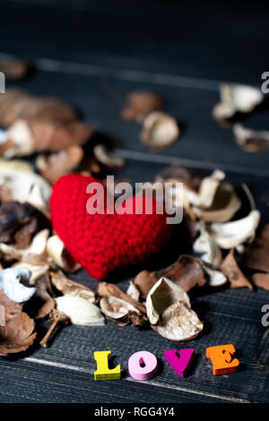 Colorful of wooden love text with aroma dried flowers and leaves. yarn red heart on the dried flowers on the black wooden table. - Stock Photo
