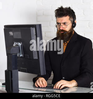 He knows how to help you. Call center operator at work. Man with long beard and headphones. Bearded man working in office. Bearded company - Stock Photo
