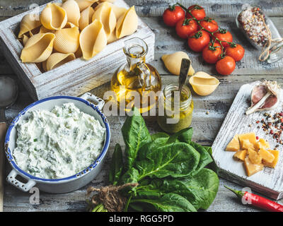 Ingredients for cooking pasta. Conchiglioni, spinach leaves, cherry tomatoes, parmesan cheese, cream cheese, olive oil, salt, garlic, rustic style, wo - Stock Photo